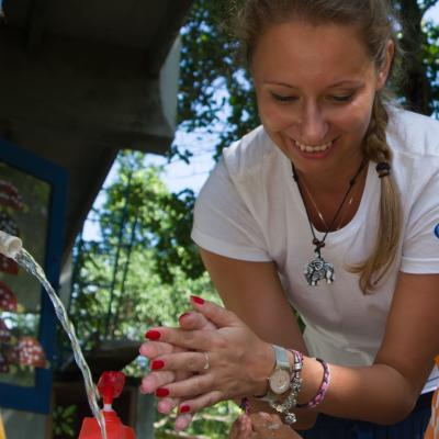 A Projects Abroad volunteer is washing her hands while volunteering abroad.